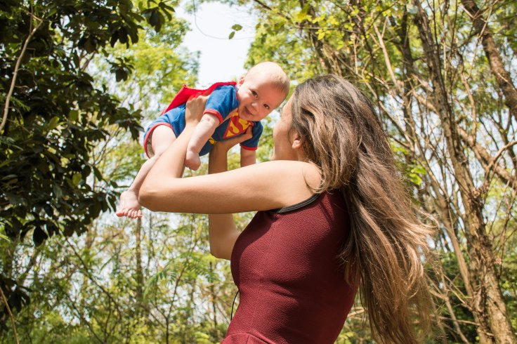 Mom holding baby in superman outfit